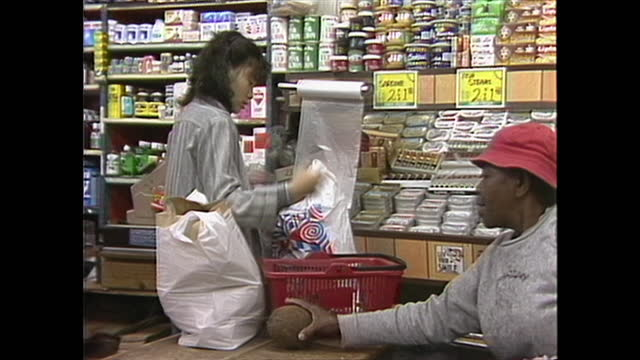 person bagging groceries inside a market in new york city's chinatown in the 1980s. - chinatown stock videos & royalty-free footage