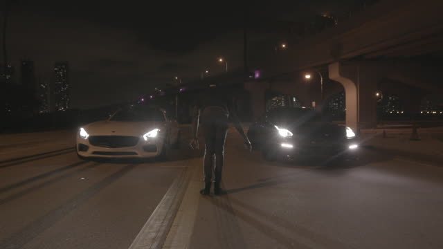 person between two sports cars gives go for drag race in miami - sportwagen stock-videos und b-roll-filmmaterial