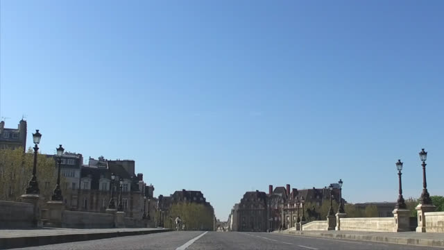 person bikes on empty new bridge with no traffic during the coronavirus epidemic on april 8 in paris, france. the country is issuing fines for people... - ポンヌフ点の映像素材/bロール