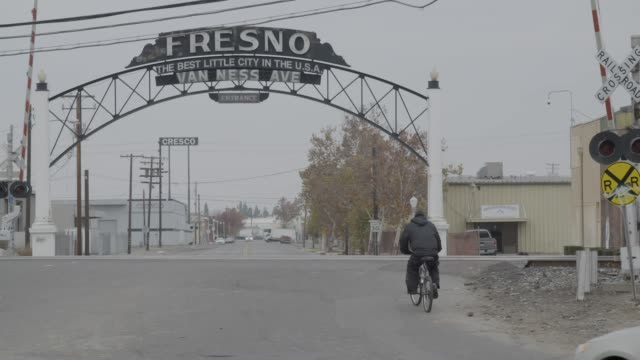 stockvideo's en b-roll-footage met person bikes under fresno welcome sign, slow motion - fresno californië