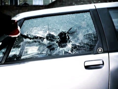 Person Breaking a Car Window With a Crowbar
