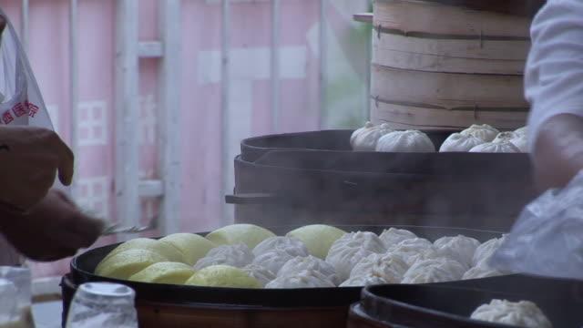 cu person buying bag of steamed dumplings from market vendor/ shenzhen, china - ダンプリング点の映像素材/bロール