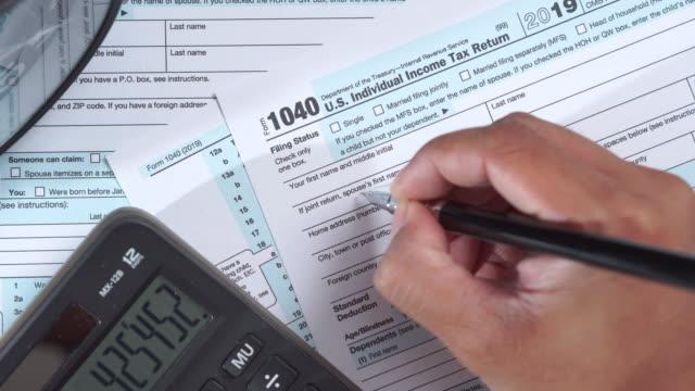 個人は、米国の税フォーム1040を計算し、記入 - 税金点の映像素材/bロール