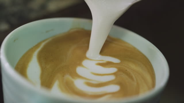 a person carefully pours steamed milk into a mug of coffee and makes latte art - pouring milk stock videos & royalty-free footage