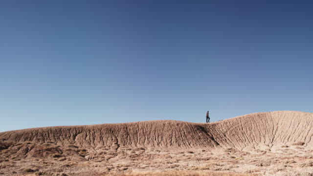 a person climbs up and walks along a striped and eroded desert mountain ridge alone against a vibrant blue sky - eroso video stock e b–roll