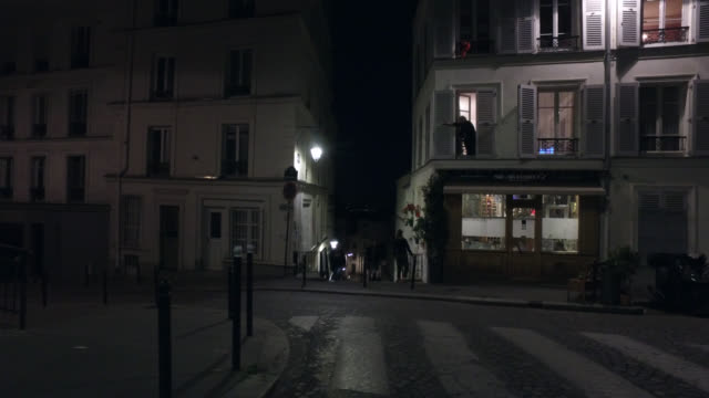 a person closes its shutters and two pedestrians building between street berthe and street andré barsacq 75018 parismay 6 2020 in paris france - three people stock videos & royalty-free footage