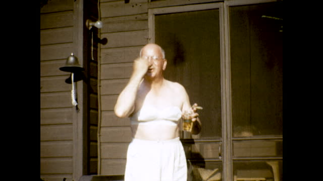 person cross-dresses in a white bikini top standing on the front porch. they have a drink and cigar in their hands. - bra stock videos & royalty-free footage