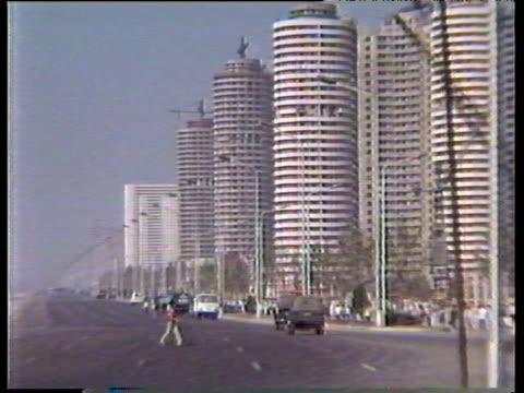 person crosses wide road with few cars cylindrical modern high rise buildings stand behind pyongyang; 1988 - north korea stock videos & royalty-free footage