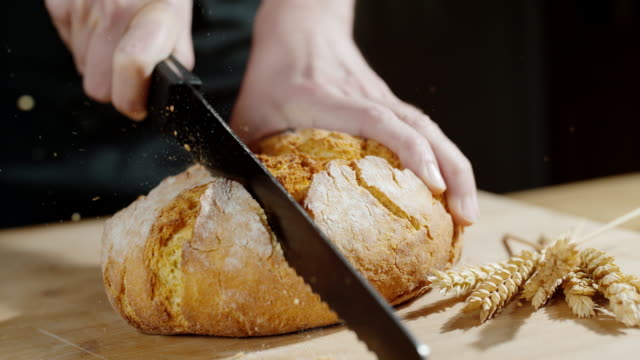 slo mo person cutting a piece of bread - bread stock videos & royalty-free footage