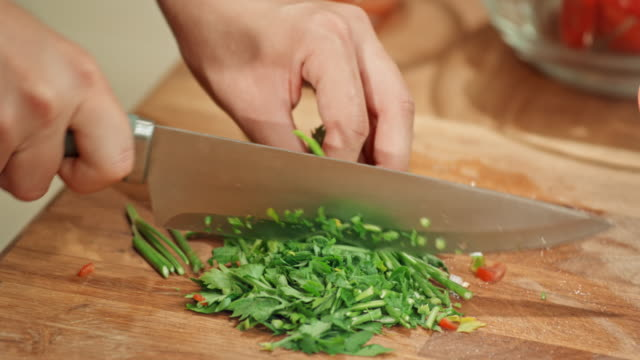 person cutting fresh herbs on a wooden board - herbs stock videos and b-roll footage