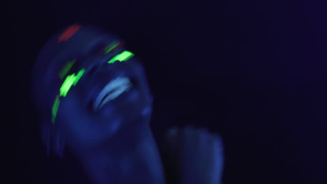 a person dancing under an ultraviolet blacklight - luce ultravioletta video stock e b–roll
