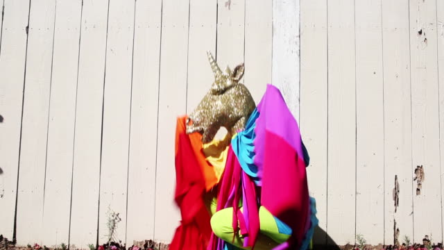 person dancing with unicorn mask and rainbow costume - eccitazione video stock e b–roll