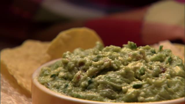 ecu, person dipping tortilla chip into guacamole dip  - dipping stock videos & royalty-free footage
