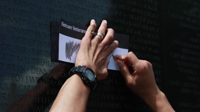A person does a rubbing of a name at the Vietnam Wall on Memorial Day
