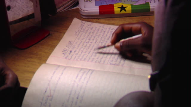 cu selective focus person doing homework notebook at night, tamale, ghana - ghana stock videos & royalty-free footage