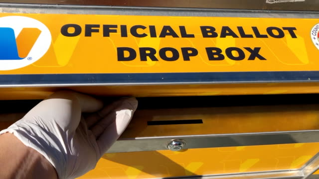 person dropping a ballot into the drop-box location in los angeles county for the 2020 presidential election. - 郵便受け点の映像素材/bロール