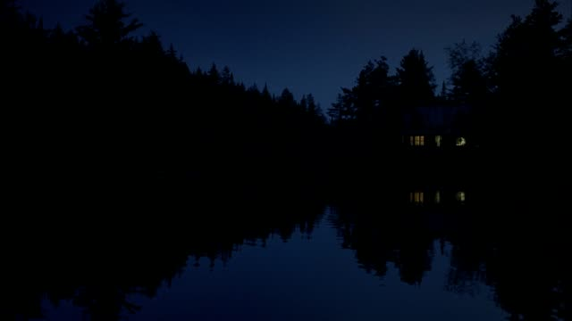 a person enters a lakeside cabin at night. - capanna di legno video stock e b–roll