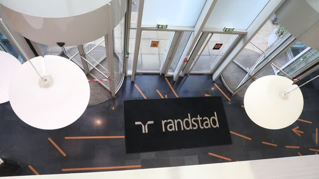 person enters the main hall at the french headquarters of the randstad company on december 4 in saint-denis, france. dutch multinational human... - クラシファイド広告点の映像素材/bロール