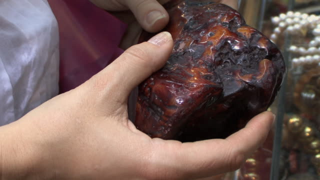 cu person examining large amber stone, muscat, oman - amber stock videos & royalty-free footage
