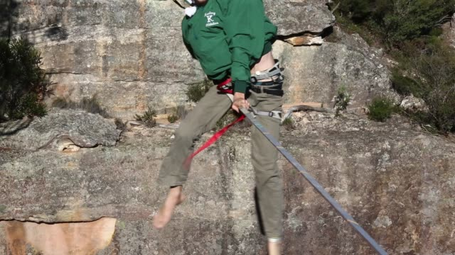 A person falls and recovers as they walk on a highline rigged between cliffs at Corroboree Walls in Mount Victoria on March 6 2015 in the Blue...