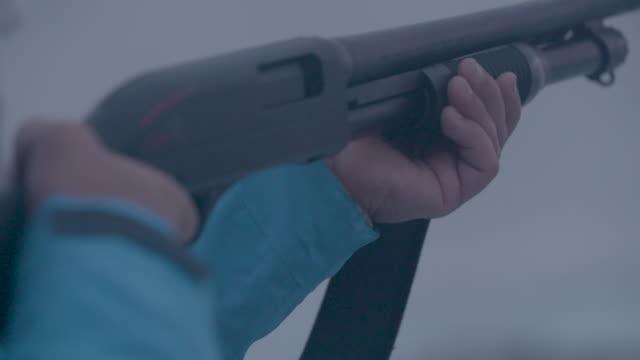 vidéos et rushes de person fires shotgun in slow motion - arme à feu