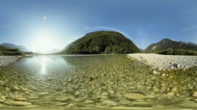 AERIAL VR 360: Person fishing in a river running in a bed of white gravel stones in sunshine