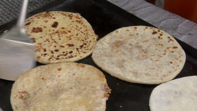 cu person flipping paranthas with aloo, or flat bread stuffed with potato, on griddle / srinagar, jammu and kashmir, india - unknown gender stock videos & royalty-free footage