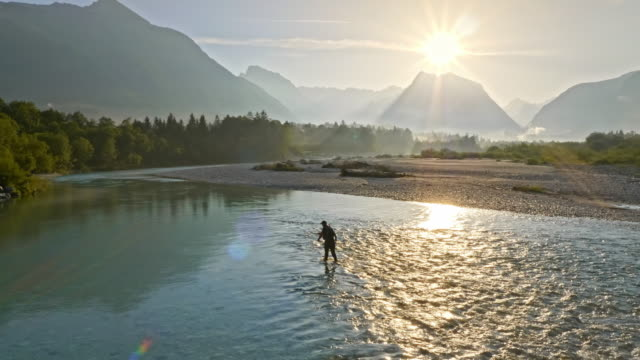 AERIAL Person fly-fishing in wonderful nature as the sun rises