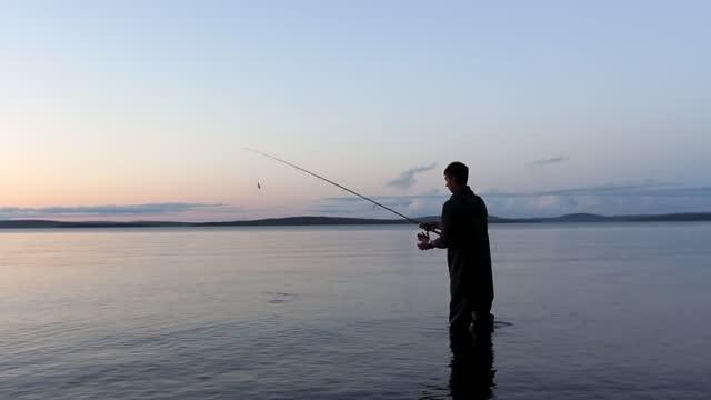 person fly-fishing on a big river as the sun is rising - camminare nell'acqua video stock e b–roll