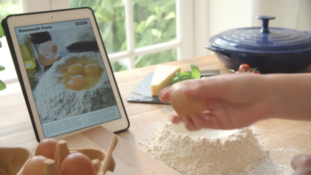 Person Following Pasta Recipe Using App On Digital Tablet