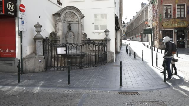 person goes by the maneken pis a major brussels landmark during the coronavirus pandemic on march 29, 2020 in brussels, belgium. the belgium... - belgium stock videos & royalty-free footage