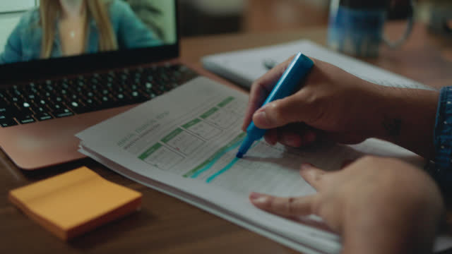 cu person highlights paperwork during a virtual call - hot desking stock videos & royalty-free footage