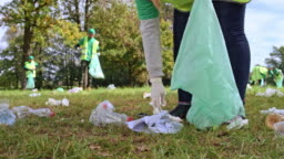 Person holding a garbage bag and picking up rubbish in the local clean-up event
