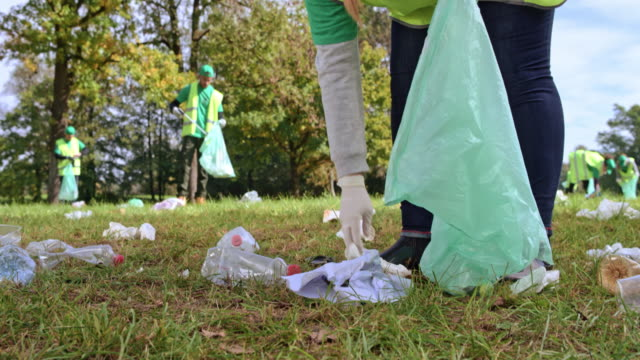 person holding a garbage bag and picking up rubbish in the local clean-up event - environmental cleanup stock videos and b-roll footage