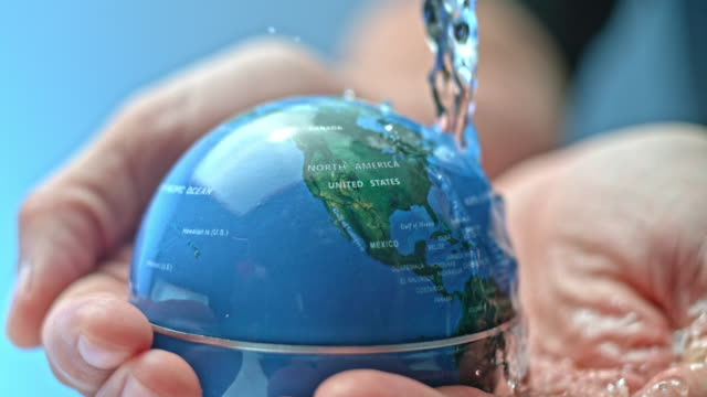 vídeos de stock e filmes b-roll de slo mo person holding a small globe that is being watered with flowing water from the top - liquid crystal display