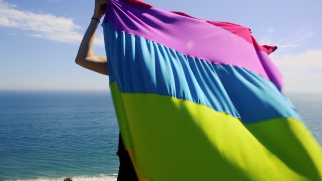 person holding rainbow flag overlooking pacific ocean - rainbow flag stock videos & royalty-free footage