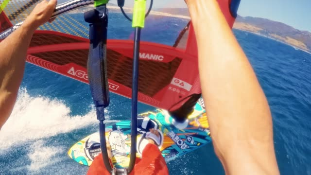 POV Person holding the boom while riding the windsurf fast across the sea