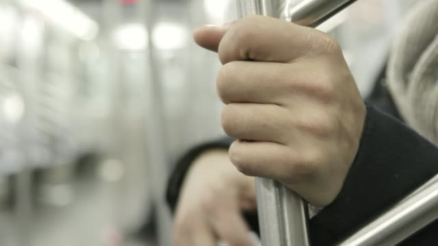 person holds subway pole, close up - stange stock-videos und b-roll-filmmaterial