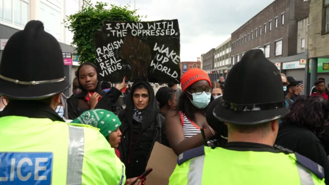 a person holds up a sign stating i stand with the oppressed while standing with other protesters behind the police forming a line during an... - african ethnicity stock videos & royalty-free footage