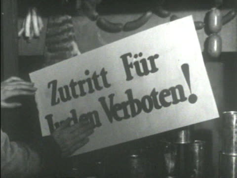 person in coat boots breaking shop front display glass ms two male hands smoothing sign 'zutritt fur juden verboten' on outside shop window ws two... - 1938 stock-videos und b-roll-filmmaterial