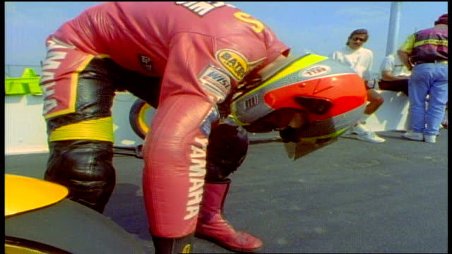 person in full racing uniform and helmet inspecting motorcycle - sportschutzhelm stock-videos und b-roll-filmmaterial
