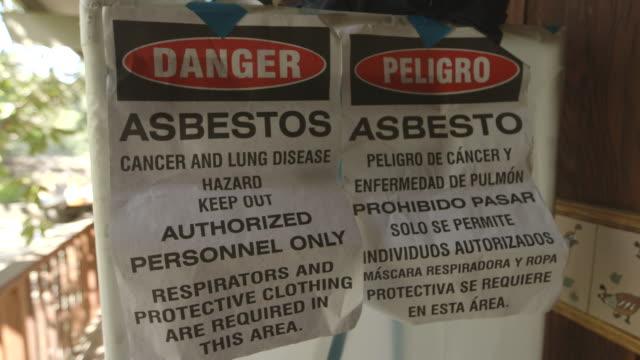 person in hazmat suit exits asbestos-ridden house, danger signs on door, close up - asbest stock-videos und b-roll-filmmaterial