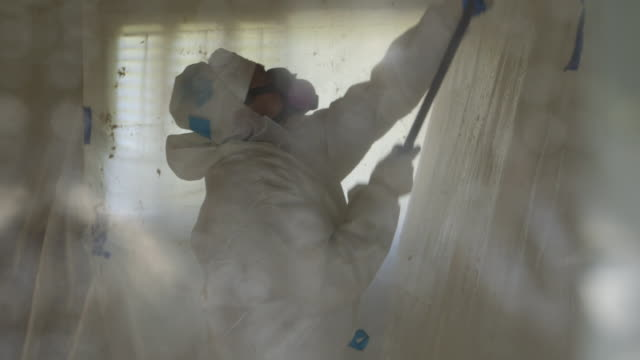 person in hazmat suits removing asbestos from home, montage - asbest stock-videos und b-roll-filmmaterial