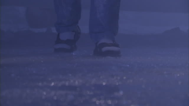 a person in jeans, socks and sandals slowly walks across slush. - socke stock-videos und b-roll-filmmaterial