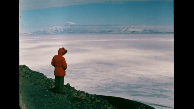 Person in red parka standing rocky cliff edge overlooking icefield w/ mountains BG TD WS Tropical animal bone exposed on melted ice male in red parka...