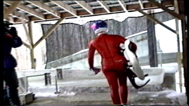 person in red suit carrying luge to track in lake placid, ny - red lake stock videos & royalty-free footage