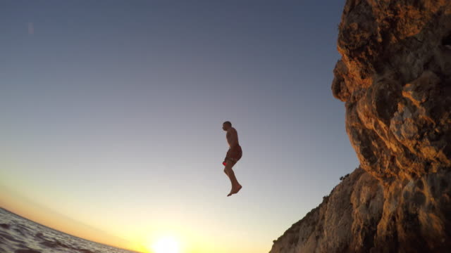 POV A person in the water watching a friend jump off a cliff at sunset