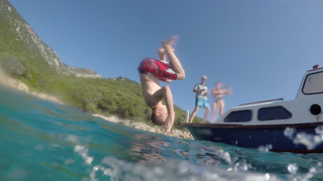 pov person in the water watching his friend jump off a boat - tuffarsi video stock e b–roll