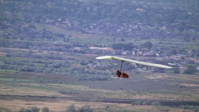 person is hang gliding near the jordan, south salt lake valley. - hang gliding stock videos and b-roll footage