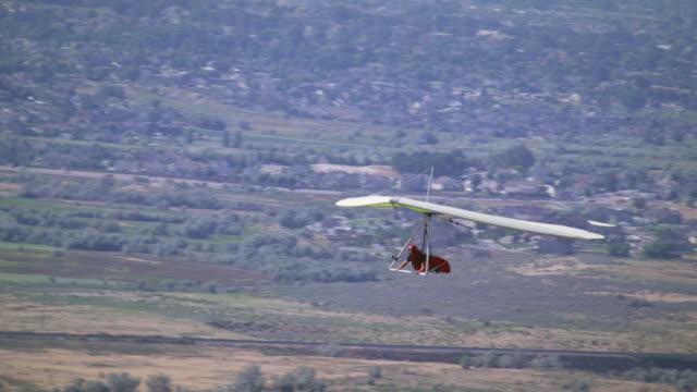 Person is Hang gliding near the Jordan, South Salt Lake Valley.